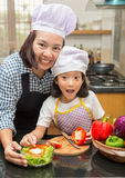 Mother teaching daughter making salad. In kitchen Stock Photo