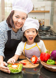 Mother teaching daughter making salad. In kitchen Royalty Free Stock Photos