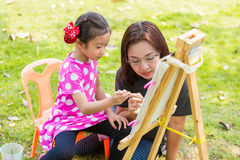 Mother teaching daughter painting Royalty Free Stock Photos