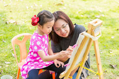 Mother teaching daughter painting Royalty Free Stock Photography