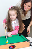 Mother teaching daughter play billiard Royalty Free Stock Image