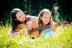 Mother teaching daughter playing guitar Stock Photography