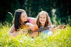 Mother teaching daughter playing guitar Royalty Free Stock Photos
