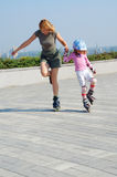 Mother teaching daughter rollerblading Royalty Free Stock Images