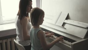 Mother teaching daughter to play piano at home. stock video footage