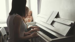 Mother teaching daughter to play piano at home. stock video