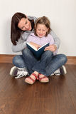Mother teaching daughter to read home education Royalty Free Stock Photo