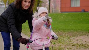 Mother teaching daughter to ride a bicycle.  stock video