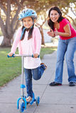 Mother Teaching Daughter To Ride Scooter. Smiling Royalty Free Stock Images