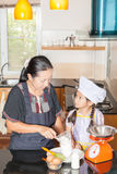 Mother teaching daughter to scooping wheat flour Stock Images