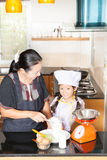 Mother teaching daughter to scooping wheat flour Royalty Free Stock Photos