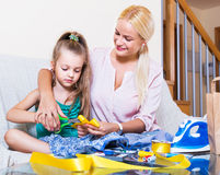 Mother teaching daughter to sew. Positive mother teaching little daughter to sew at home Stock Images