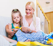 Mother teaching daughter to sew. Young mother teaching her little daughter to sew at a home Royalty Free Stock Photo