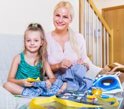 Mother teaching daughter to sew Royalty Free Stock Images