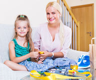 Mother teaching daughter to sew Stock Image