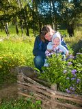 Mother teaching flowers her baby. Woman teaching botany flowers her kid in the fall garden Royalty Free Stock Image