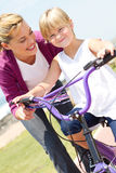 Mother teaching girl ride bicycle Stock Photography