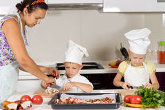Mother teaching her children to cook Royalty Free Stock Images