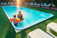 Mother teaching her children to swim. In pool Royalty Free Stock Photo