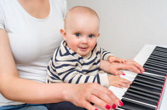 Mother teaching her cute baby to play piano Royalty Free Stock Image
