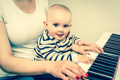 Mother teaching her cute baby to play piano - retro style. Mother teaching her cute baby to play piano at home - retro style Stock Photos