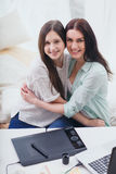 Mother teaching her daugher to draw by stylus. Beautiful women and pretty teenager girl drawing illustrations together with digital tablet and stylus Royalty Free Stock Image