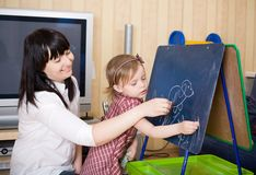Mother teaching her daughter. Drawing sketches on blackboard. Prepare to school series Stock Photo
