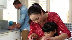Mother teaching her daughter cutting vegetables. In kitchen stock video footage