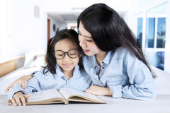 Mother teaching her daughter at home Stock Image