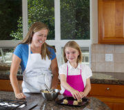 Mother teaching her daughter how to make cookies from raw dough Stock Image
