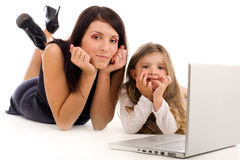 Mother teaching her daughter how to use laptop. Young mother teaching her daughter how to use laptop and internet Stock Photography