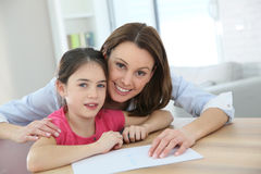 Mother teaching her daughter how to wite Royalty Free Stock Photos