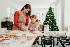 Mother and daughter making Christmas cookies. Mother teaching her daughter to make cookies. Little girl sifting flour for making cookies Stock Image