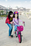Mother teaching her daughter to ride bicycle Royalty Free Stock Images