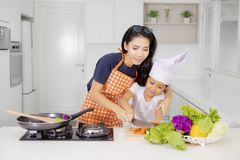 Mother teaching her daughter to slice a carrot Stock Image