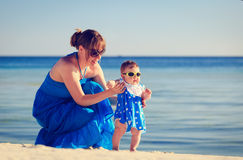 Mother teaching her daughter to walk on beach Stock Photo