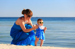 Mother teaching her daughter to walk on beach Royalty Free Stock Photo