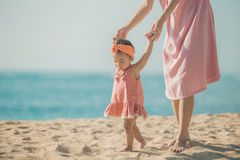 Mother is teaching her daughter walks on the beach stock photos