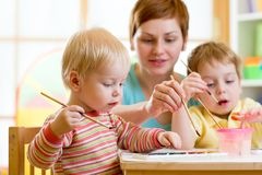 Mother teaching her kids to paint. Cute mother teaching her kids to paint Royalty Free Stock Photos