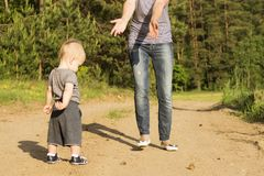 Mother teaching her one year baby boy son for walking. Shy toddler trying to make first steps royalty free stock image