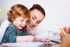 Mother teaching her son drawing Stock Photos