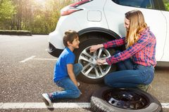 Mother teaching her son to change a wheel of car stock photography