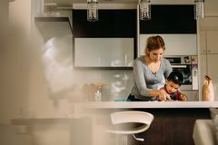 Mother teaching her son to make cookies. Woman with her son making cookies at home kitchen stock image