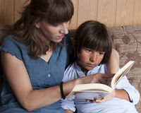 Mother teaching her son to read. A book Royalty Free Stock Photography
