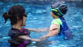 Mother is teaching her son to swim stock footage