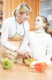 Mother Teaching Her Teenage Daughter  to Cook Salad in The Kitch Stock Photos