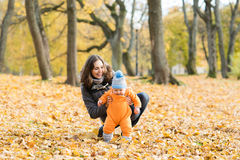 Mother teaching her toddler son to walk in the park Stock Photos