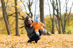 Mother teaching her toddler son to walk in the park Stock Images