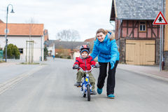 Mother teaching her 3 years old son to ride a bike Stock Photo