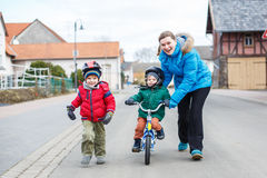 Mother teaching her 2 years old son to ride a bike Stock Photography